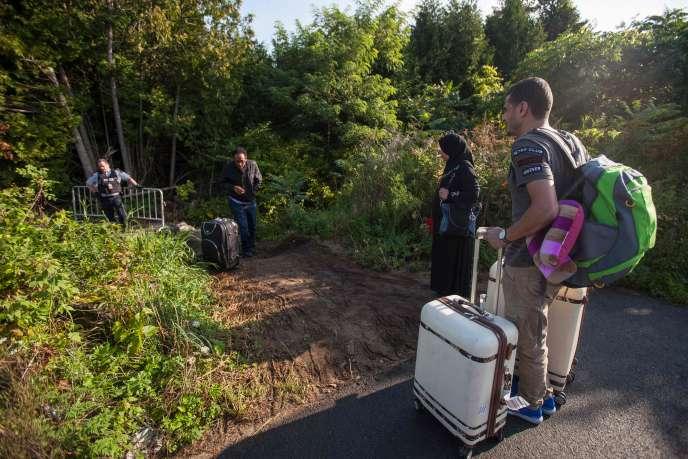 Des migrants se préparent à traverser illégalement la frontière canado-américaine, près de Hemmingford, au Québec (Canada), le 20 août 2017.